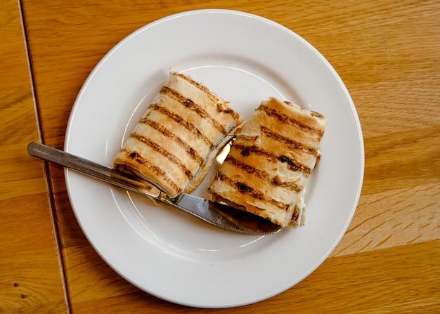 Pokrojona kanapka na białym talerzu na stole w kawiarni