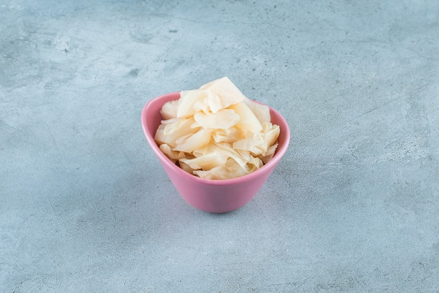 Pokrojona kiszona kapusta z marchewką w plastikowej misce na niebieskiej powierzchni