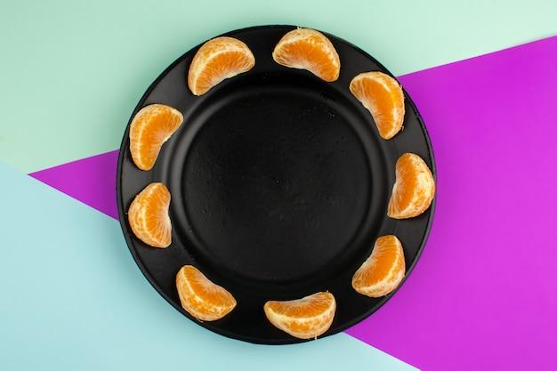 Pokrojona mandarynkowa kwaśna soczysta łagodność w środku czarny talerz na kolorowej podłodze
