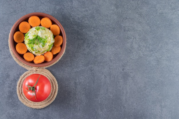 Pokrojona marchewka i surówka w misce obok pomidorów na trójnogu na niebieskiej powierzchni