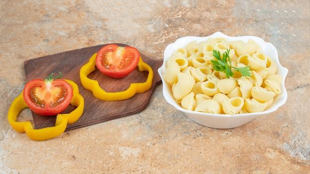 Pokrojona papryka i pomidory na desce do krojenia obok miski makaronu fajkowego na marmurowej powierzchni