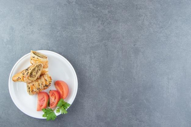 Pokrojona pleciona bułka nadziewana mięsem na białym talerzu.