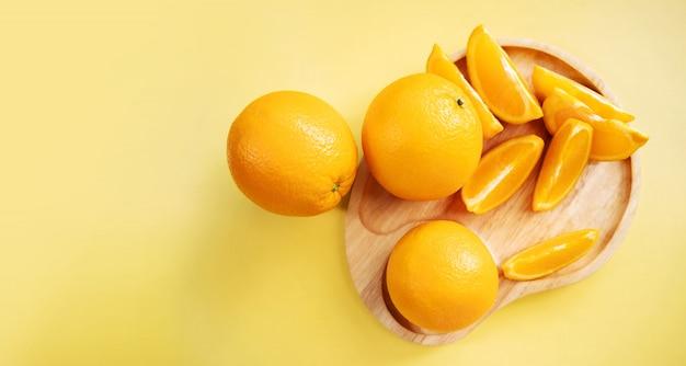 Pokrojona pomarańcze na drewnianym talerzu. świeża soczysta owoc w lecie.