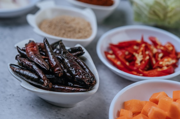 Pokrojona w kostkę marchewka, suszone chilli, prażony ryż i pasta chili na cementowej podłodze.