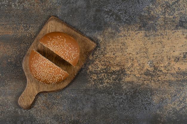 Pokrojona w pół smaczna bułka z sezamem na drewnianej desce.