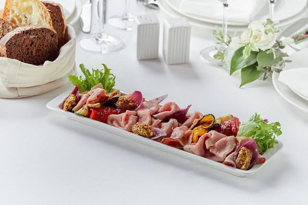 Pokrojona wołowina lub wieprzowina z marynowanymi warzywami i sosem