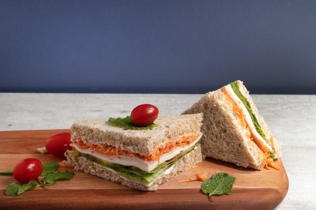 Pokrojona zdrowa kanapka z integralnego chleba nadziewana marchewką, sałatą, mozzarellą i szynką.