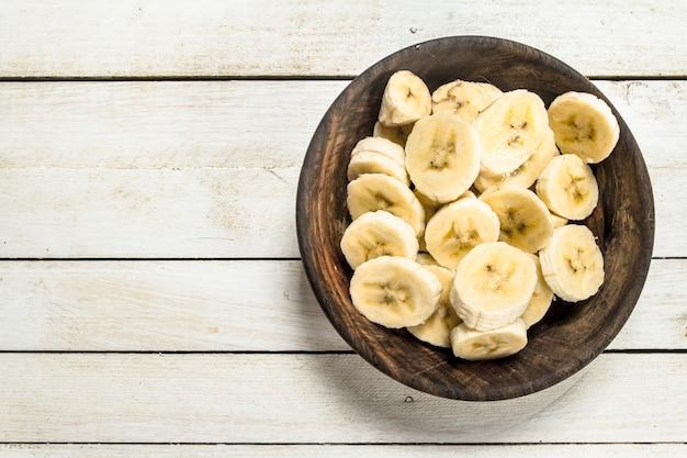 Pokrojone banany w drewnianej misce na białym drewnianym stole.