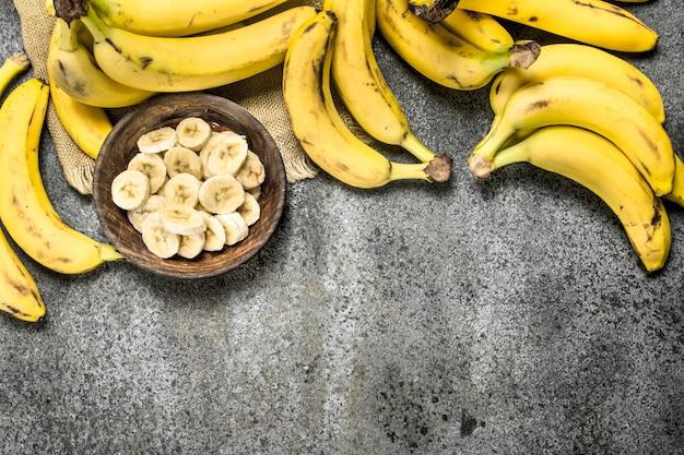 Pokrojone banany w misce na rustykalnym stole.