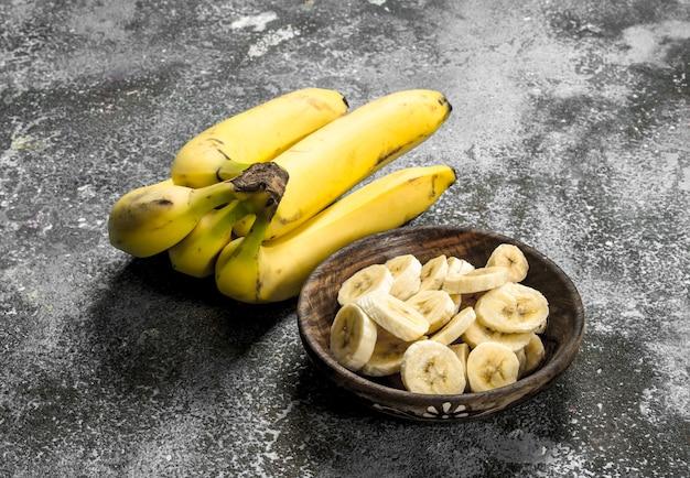 Pokrojone banany w misce. na rustykalnym stole.