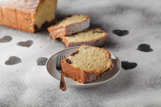 Pokrojone ciasto i serce mąki na drewnianym biurku