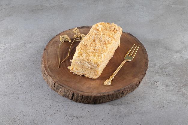Pokrojone ciasto i widelec na desce na marmurowej powierzchni