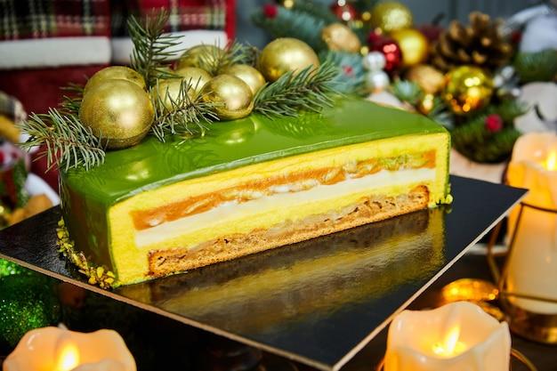 Pokrojone ciasto świąteczne o tropikalnych smakach ozdobione czekoladowymi bombkami