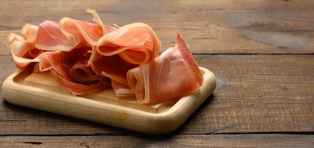 Pokrojone cienkie plasterki prosciutto na drewnianej brązowej desce, drewniany stół tło
