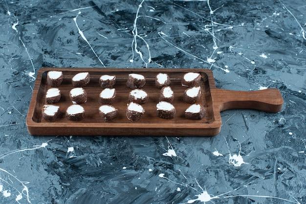 Pokrojone cukierki na desce, na niebieskim stole.