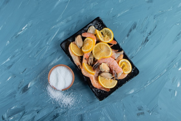 Pokrojone cytryny i krewetki na półmisku obok solniczki na marmurowej powierzchni.