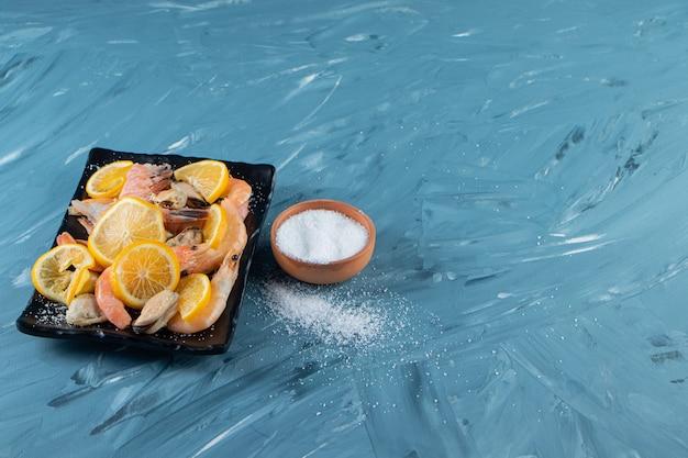 Pokrojone cytryny i krewetki na półmisku obok solniczki, na marmurowym tle.