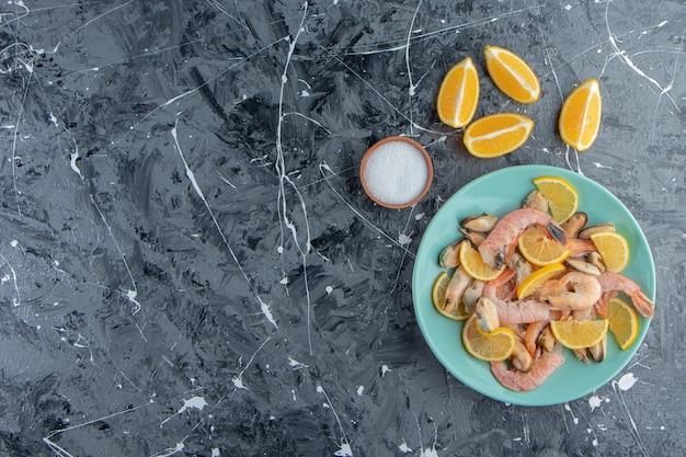 Pokrojone cytryny i krewetki na talerzu obok miski na sól, na marmurowym tle.