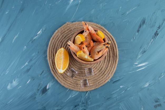Pokrojone cytryny i krewetki w misce na podstawce, na marmurowym tle.