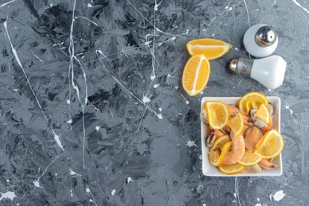 Pokrojone cytryny i krewetki w misce obok soli, na marmurowym tle.