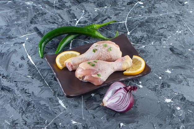 Pokrojone cytryny i podudzia na półmisku obok warzyw na marmurowej powierzchni.