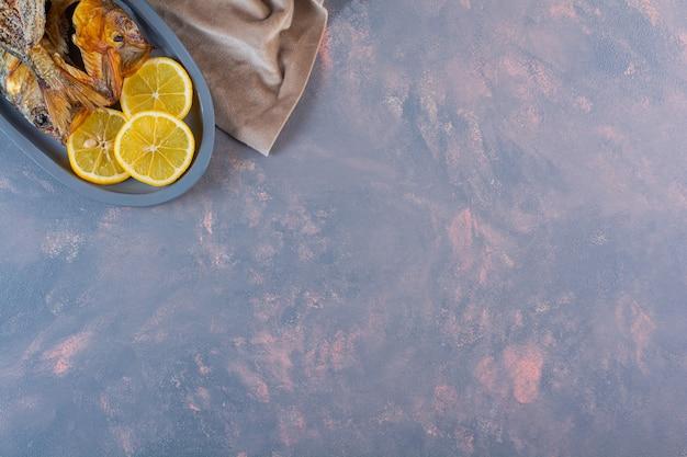 Pokrojone cytryny i suszoną soloną rybę na drewnianym talerzu, na marmurowej powierzchni