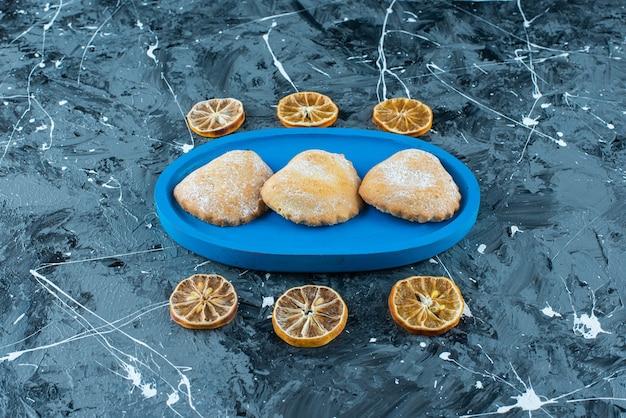 Pokrojone cytryny obok ciast na drewnianym talerzu, na niebieskim stole.