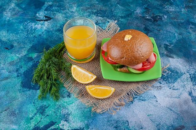 Pokrojone cytryny, szklankę soku i kanapkę na talerzu, na niebieskiej powierzchni.