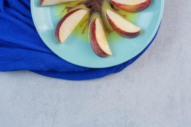 Pokrojone czerwone żółte jabłka w niebieskim talerzu.