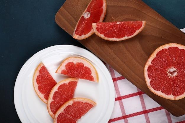Pokrojone grejpfruty w białym talerzu i na drewnianej desce.
