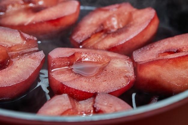 Pokrojone gruszki gotuje się w czerwonym syropie z winem na kuchence gazowej