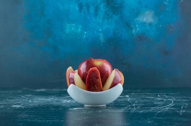 Pokrojone i całe czerwone jabłko w białej misce.