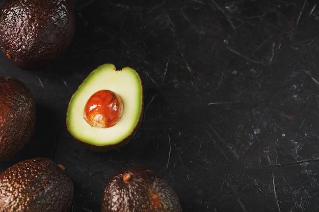 Pokrojone i całe organiczne awokado hass z nożem na czarnej powierzchni. źródło niezbędnych tłuszczów, witamin, pierwiastków śladowych, beta-karotenu i kwasów tłuszczowych omega-3.