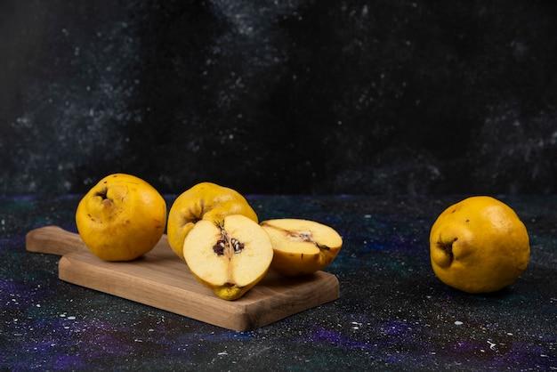 Pokrojone i całe świeże owoce pigwy na desce.