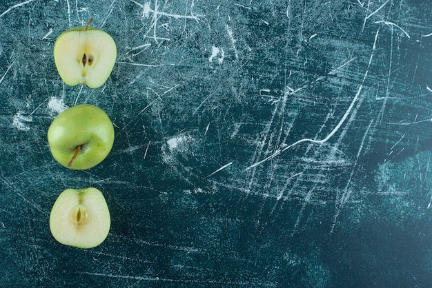 Pokrojone i całe zielone jabłka na marmurowym stole.