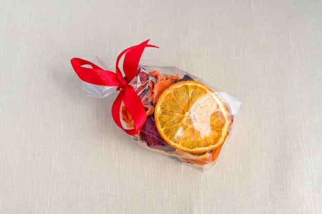 Pokrojone i suszone jabłko, pomarańcza, marchew i buraki w opakowaniu prezent na tle włókienniczych.