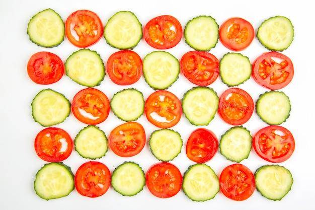 Pokrojone kawałki ogórka i pomidora na białym tle. fast food i śniadanie?