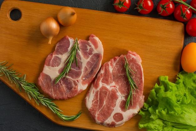 Pokrojone kawałki surowego mięsa do grillowania na drewnianej powierzchni, przepisy kulinarne menu. jedzenie, surowy stek, grillowany stek wołowy, pomidory, papryka, przyprawy do gotowania mięsa