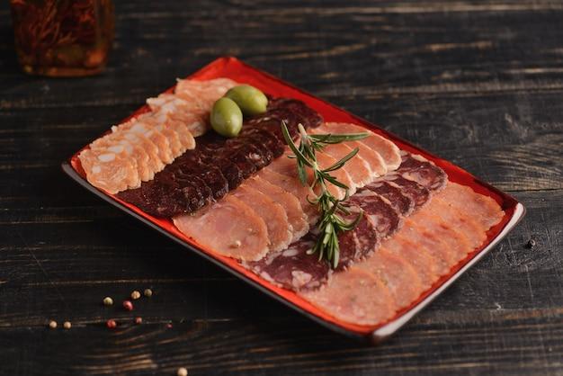 Pokrojone kiełbasy na czerwonym talerzu. z rozmarynem i oliwkami. na drewnianym stole