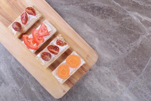 Pokrojone marchewki i pomidory na chrupiącym pieczywie, na marmurowej powierzchni