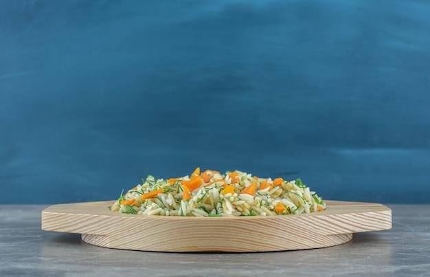 Pokrojone marchewki i ryż na drewnianym talerzu, na ręczniku, na marmurowym stole.