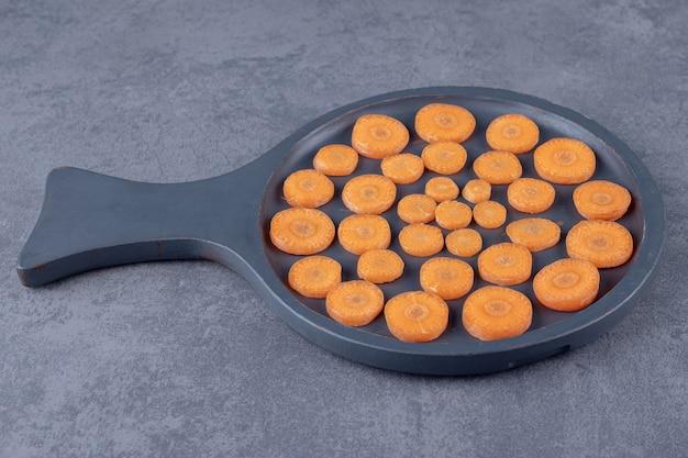 Pokrojone marchewki na patelni, na marmurowej powierzchni.