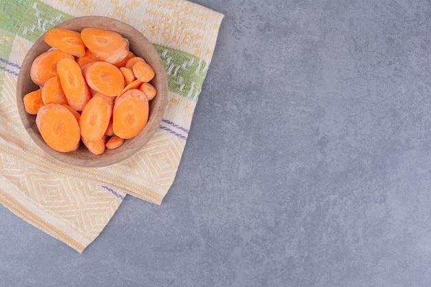 Pokrojone marchewki w drewnianym kubku na stole