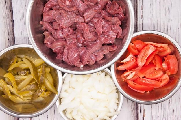 Pokrojone mięso wołowe lub wieprzowe ze świeżymi warzywami widok z góry