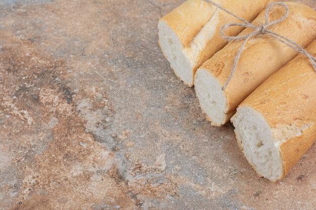 Pokrojone na pół chleb bagietki na tle marmuru