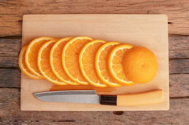 Pokrojone owoce pomarańczy i nóż na desce do krojenia