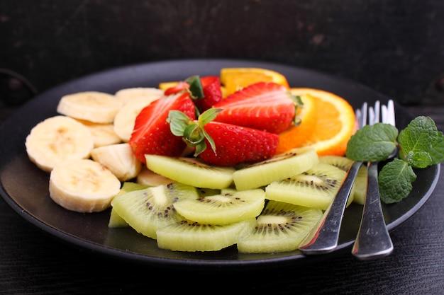 Pokrojone owoce (truskawki, kiwi, pomarańcza, banan) na czarnej płycie