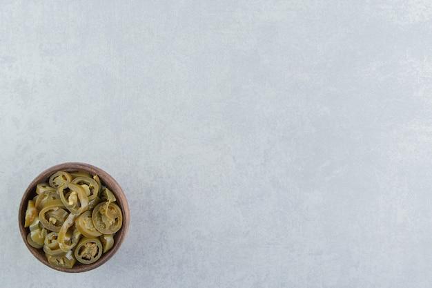 Pokrojone pikle papryczki jalapeno w misce, na marmurowej powierzchni