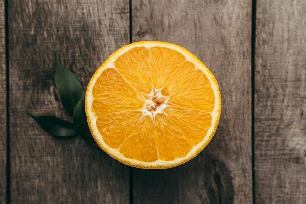 Pokrojone połówki pomarańczy na szarym tle drewnianych. miazga i zielone liście