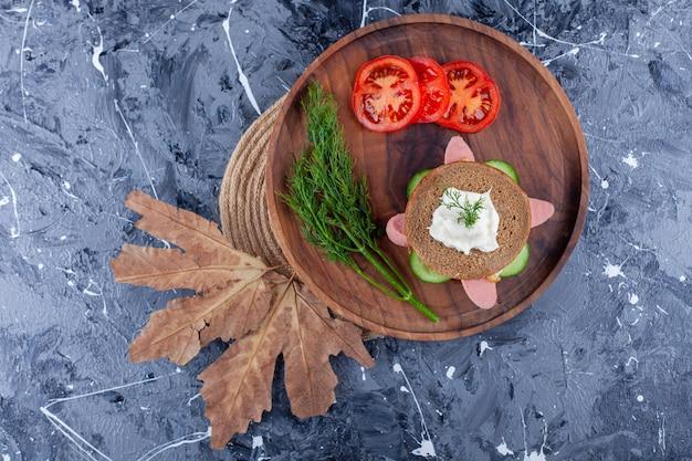 Pokrojone pomidory, koperek i kanapkę na desce, na niebieskiej powierzchni.